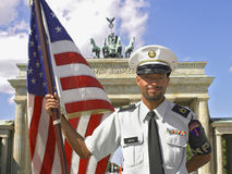 Soldier at Brandenburg. BERLIN, GERMANY: Unidentified MP soldier  holding American flag in front of the Brandenburg gate, Germany Royalty Free Stock Photo