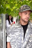 Soldier leaving home as wife watches on stock photo