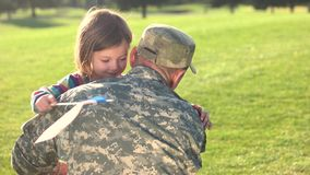 Soldier in camoubackgrounde hugging his daughter in the park. stock video