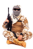 Soldier in camouflage and arabian scarf holding a rifle. On white background Stock Photos