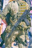 Soldier in camouflage with a gun behind his back. A soldier in camouflage with a gun behind his back. Rear view stock photography