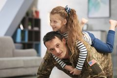 Soldier in camouflage playing with his daughter. At home royalty free stock images