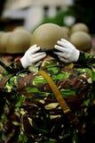 Soldier in camouflage uniform arranging hi helmet Stock Photos