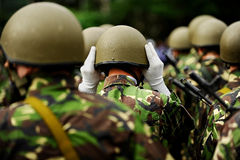 Soldier in camouflage uniform arranging his helmet Royalty Free Stock Photo
