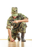 Soldier in camouflage uniform and hat kneeling on the floor and Stock Photos