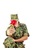 Soldier in camouflage uniform kneeling holding flower Royalty Free Stock Photo