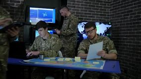 Soldier in camouflage uniform, view maps and working in laptoop, military headquarters, briefing in monitoring room, stock video footage