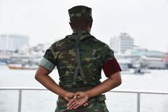 Soldier in camouflage uniforms, hands behind his backs. royalty free stock image