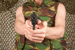 Soldier in camouflage vest is holding a gun Royalty Free Stock Photo