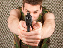 Soldier in camouflage vest is holding a gun Stock Photography
