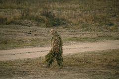 Soldier in camouflaged sniper suit searching position stock photos