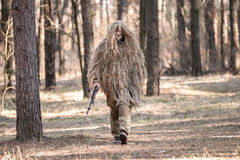 Soldier in camouflaged sniper suit  walking with gun. In forest.Selective focus Stock Images