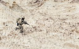 Soldier with carbine running alone through desert royalty free stock images