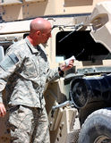 A soldier checking vehicle. A soldier in uniform checking oil in a tactical vehicle Royalty Free Stock Photography