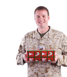 Soldier with Christmas Present. A military man holds a Christmas gift Royalty Free Stock Photography