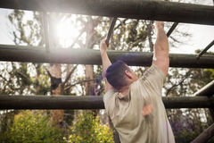 Soldier climbing monkey bars. In boot camp Stock Photos