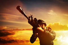 Soldier in combat shooting with his weapon, rifle. War, army concept Royalty Free Stock Photography