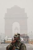 Soldier coughing in smog with India Gate behind Royalty Free Stock Photography