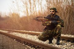 Soldier with crossbow. The army soldier in military uniform with crossbow weapon is on railroad track outdoors Stock Image