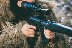 The soldier disguised in a balaclava and military camouflage aims at the sight of a sniper rifle. Stock Image
