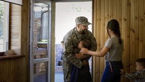 Soldier entering home with happy family. Serviceman walking inside of house and meeting with cheerful happy kids and wife after army service stock photo