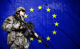 Soldier on European Union flag background. Soldier holding rifle on a European Union flag background royalty free stock images