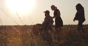 Soldier and family enjoying afternoon on a meadow. Tracking shot of a wheelchaired soldier and his family enjoying the afternoon on a meadow stock footage