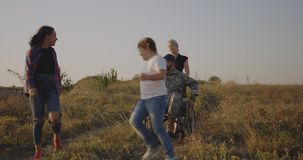 Soldier and family enjoying afternoon on a meadow. Tracking shot of a wheelchaired soldier and his family enjoying the afternoon on a meadow stock video footage