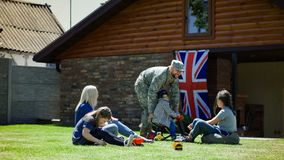 Soldier with family enjoying time outside. Soldier in uniform chilling on lawn with family spending time with kids on background of house with British flag royalty free stock photos