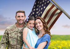 Soldier with family in front of usa flag in the field. Digital composite of soldier with family in front of usa flag in the field royalty free stock photo