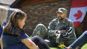 Soldier with family on green backyard. Military men in uniform sitting on lawn with wife and kids while relaxing on backyard of house in sunlight royalty free stock image