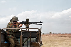 Soldier fires a machine gun Stock Images