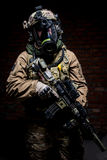 Soldier in gas mask with rifle in hands royalty free stock photo