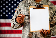 Soldier: Gesturing to Blank Paper on Clipboard. Series with an anonymous African-American soldier on a United States Flag background stock photos
