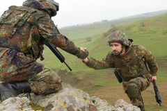 Soldier gives hand to his partner. Military man helping his friend to climb up the rock Royalty Free Stock Photography