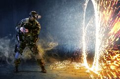 Soldier in glasses of virtual reality. The concept of virtual re. A soldier with virtual reality glasses looks at the ring of fire and holds a gun in his hands Stock Photos