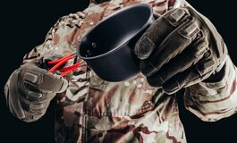 Soldier in gloves holding metal cup