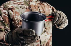 Soldier in gloves holding metal dish cup