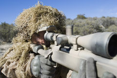 Soldier In Grass Camouflage Pointing Rifle Stock Image