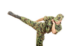 Soldier in a green camouflage uniform kicking Royalty Free Stock Photo