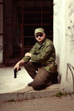 Soldier guarding building with pistol Stock Photography