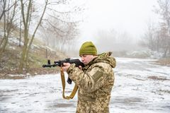 A soldier with a gun aims and shoots at the enemy, defending his homeland.  stock photo