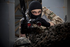 Soldier with gun and binoculars stock image