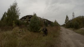 Soldier with gun in hand goes to the abandoned building stock video footage