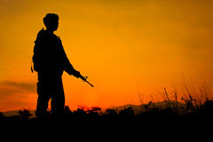 Soldier and gun in silhouette shot Royalty Free Stock Photos