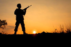 Soldier and gun in silhouette shot. Silhouette shot of soldier holding gun with colorful sky and mountain in backgroud royalty free stock photo