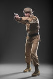 Soldier with a gun takes aim on dark background Royalty Free Stock Images