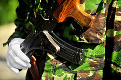 Soldier hand on AKM rifle Stock Photo