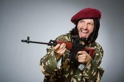Soldier with handgun against gray Stock Photo