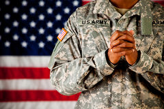 Soldier: Hands Clasped in Prayer. Series with an anonymous African-American soldier on a United States Flag background stock image